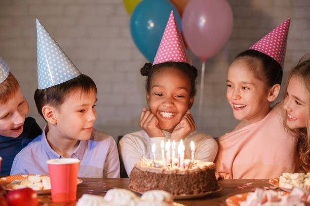 African-american girl looking at birthday cake, having party with friends